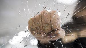 Käsi rikkoo ikkunan lähikuvassa.
