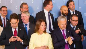 EU:n kauppaministerit luokkakuvassa. Vasemmassa reunassa Ranskan ministeri katsoo kännykkäänsä. Kolme ministeriä tarkastelee kellojaan.