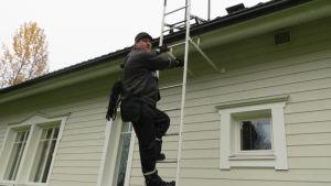 Nuohooja Mika Hagert kiipeämässä katolle