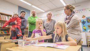 Lapsia ja aikuisia Kuuslahden koulun luokassa
