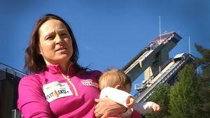 Aino-Kaisa Saarinen tyttärensä kanssa Lahden urheilukeskuksessa.