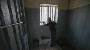 Lavastetussa kuvassa vanki katsoo kaltereiden takaa sellistään ulos.