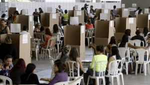 Ihmisiä istuu valkoisilla muovituoleilla suuressa huoneessa, jossa näkyy pahvisia äänestyskoppeja.