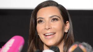 Kim Kardashianin kasvokuva. Edessä mikrofoneja.