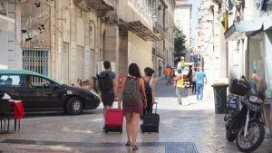 Helleasuiset turistit vetävät matkalaukkuja.