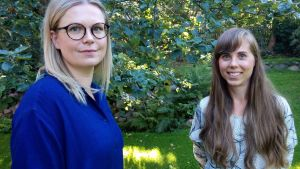 Toimitusjohtaja Johanna Vaissi ja vaatesuunnittelija Outi Mäkinen seisovat puutarhassa omenapuiden alla aurinkoisena syyspäivänä.