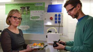 Nainen ja mies esittelevät biojätteenkäsittelylaitteistoa