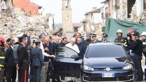 Paavi menossa autoon kadulla, jonka talot ovat raunioina. Auton ympärillä on suuri joukko ihmisiä, muun muassa poliiseja.