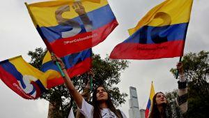 Naispuoliset opiskelijat heiluttavat lippuja ja kannattavat rauhansopimusta äänestyksen alla Bogotassa Kolumbiassa.