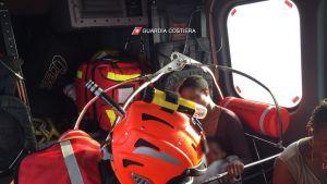 Kaksi siirtolaisnaista istuu helikopterin kyydissä. Toisella naisella on lapsi sylissään. Etualalla häärää rannikkovartioston työntekijä punaisissa liiveissä ja oranssi kypärä päässään.