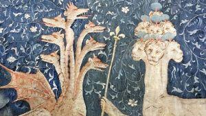 Seitsenpäinen lohikäärme ja seitsenpäinen sarvekas leijona taistelevat valtikasta sinisten levien katveessa.