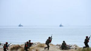 Sotilaat juoksevat hiekassa, taustalla meri jossa kaksi alusta.