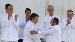 Kolumbian presidentti Juan Manuel Santos (edessä vas.) ja sissiliike Farcin johtaja Rodrigo Londoño Echeverri iloitsivat rauhansopimuksen allekirjoittamisen jälkeen Kolumbian Cartagenassa syyskuussa