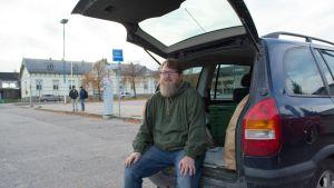 Kalle Hoppula istuu auton peräkontin reunalla.