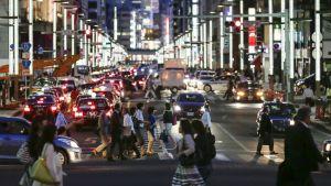 Kuva vilkkaasta risteyksestä, ihmiisä ylittämässä katua, takana autojen valot. On ilta.
