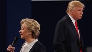 Hillary Clinton ja Donald Trump selin toisiinsa vaaliväittelyn aikana. Mikrofoni on Clintonilla.