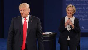 Trump seisoo etualalla, Clinton taempana. Trumpin ilme on vakava, Clinton hymyilee.