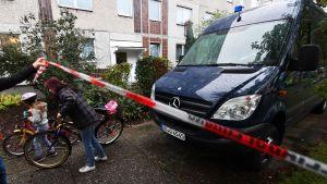 Poliisi saattaa naista ja lasta pois kerrostalon pihalta.