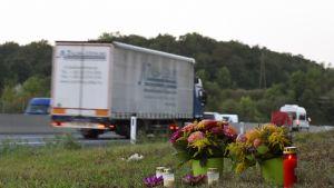 Kukkia ja kynttilöitä pientareella, takana valkoinen rekka.