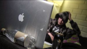 nuori nojaa sohvalla tietokone pöydällä