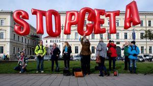 Pieni joukko mielenosoittajia, jotka pitelevät punaisia kirjaimen muotoisia ilmapalloja, jotka muodostavat lauseen Stop CETA.