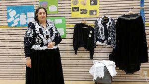 Kuvassa romaninainen, romaninaisen vaatteita sekä tietoiskujulisteita romaneista