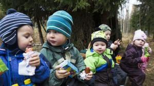 Lapset syövät makkaraa metsäretkellä