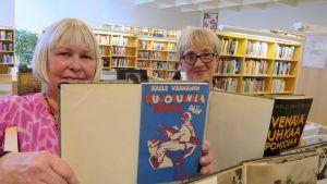 Kaksi naista pitävät kirjastossa käsissään vanhoja kirjoja