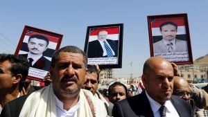Jemeniläiset pitelivät mielenosoituksessa Sanaassa kuvia uhreista, jotka olivat saaneet surmansa Saudi-Arabian johtaman liittouman hautajaisiin tekemässä ilmaiskussa
