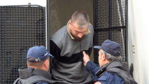 Kaksi montenegrolaispoliisia saattaa kiinniotettua serbimiestä.