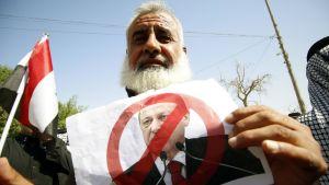 Mielenosoittajia pitää kädessään presidentti Erdoganin kuvaa. Basrassa Etelä-Irakissa.