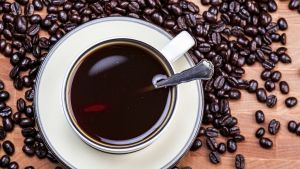 Kahvikuppi kuvattuna ylhäältä - kahvinpapuja taustalla.