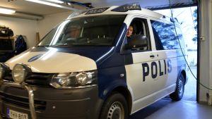 Naispoliisi poliisiautossa.