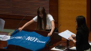 """Kansanedustaja levittää pöydälle hallintoelimen ensimmäisessä kokouksessa 12. lokakuuta lipun, jossa lukee """"Hongkong ei ole Kiina""""."""