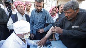 Lääkäri tutkiin syyrialaisen miehen kättä.