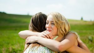 Kaksi naispuolista ystävää halaa toisiaan.
