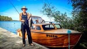 Juhani Olkkola veneen äärellä kädessään ennätysahven Lestijärvestä