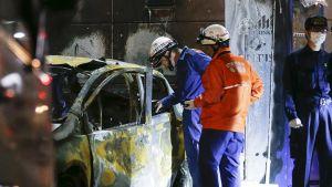 Palolaitoksen tutkijat tarkastelevat räjähdyksessä tuhoutuneen auton jäänteitä Utsunomya Joshi -puiston lähistöllä.