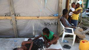 Koleraoireista kärsivä nainen makaa maassa Haitissa.