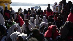 Suuri joukko ihmisiä istuu laivan kannella. Taustalla näkyy vene ja rannikkoa.