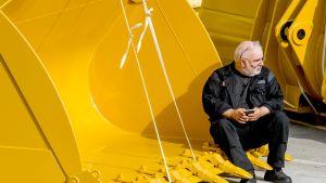 mies istuu Caterpillarin kauhassa