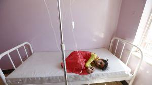 Sairaalan sängyllä makaa pienellä kerällä tummahiuksinen laiha tyttö punainen mekko ja keltainen paita yllään, tyttö pitää kiinni tippaletkusta.