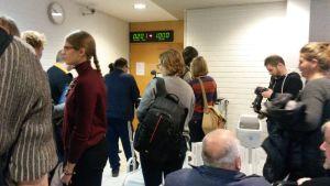 Yleisö ja media Oulun käräjäoikeuden aulassa istuntosalin edessä.