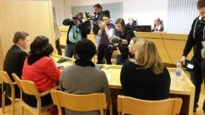 Media ottaa kuvia Oulun käräjäoikeuden istuntosalissa lokakuussa 2016. Taustalla käräjätuomari.