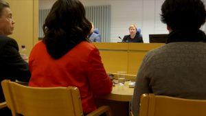 Oulun käräjäoikeuden istuntosali, tuomari pöydän takana, asianomistaja avustajan kanssa selin istumassa.
