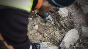 Henkilö tekemässä arkeologisia kaivauksia.