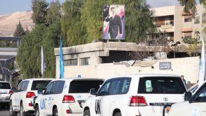YK:n henkilöautoja kulkee ohi rakennuksen, jota koristaa presidentti Bashar al-Assadin kuva.
