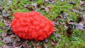 Pellen punainen peruukki maassa.