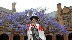Kate Blanchett seisoon yliopiston sisäpihalla jakarandapuun edessä.