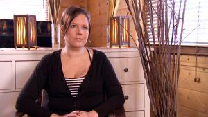 Regina Kankaanpää istuu nojatuolissa kotonaan.